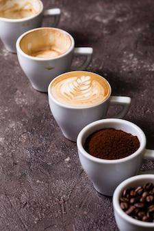 Ukośne pięć filiżanek różnych etapów przygotowania cappuccino. koncepcja miłośnika kawy martwa natura