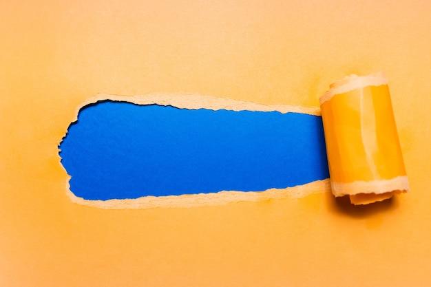 Ukośnie rozdarty żółty papier z miejsca kopiowania tekstu fantomowego koloru niebieskiego.