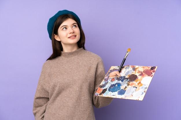 Ukraińska młoda artysta kobieta trzyma paletę nad izolowanym fioletowym murem patrząc w górę, uśmiechając się