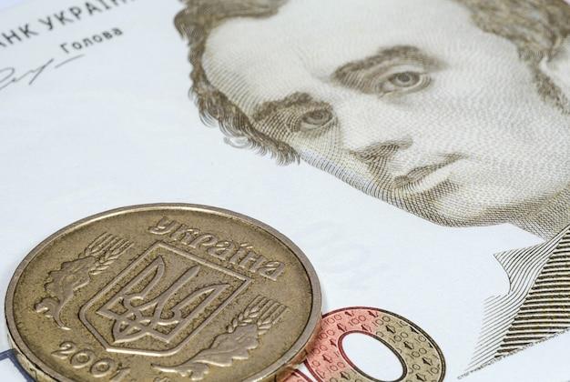 Ukraińska moneta na banknocie stu hrywien z bliska