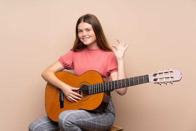 Ukraińska nastolatek dziewczyna z gitarą nad odosobnionym pokazuje ok znakiem z palcami