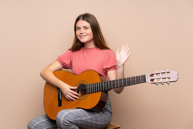 Ukraińska nastolatek dziewczyna z gitarą nad odosobnionym salutować ręką z szczęśliwym wyrażeniem