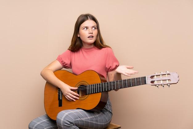 Ukraińska nastolatek dziewczyna z gitarą nad odosobnionym z niespodzianka wyrazem twarzy