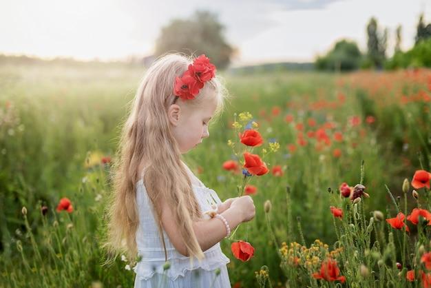 Ukraińska piękna dziewczyna w dziedzinie maków i pszenicy.