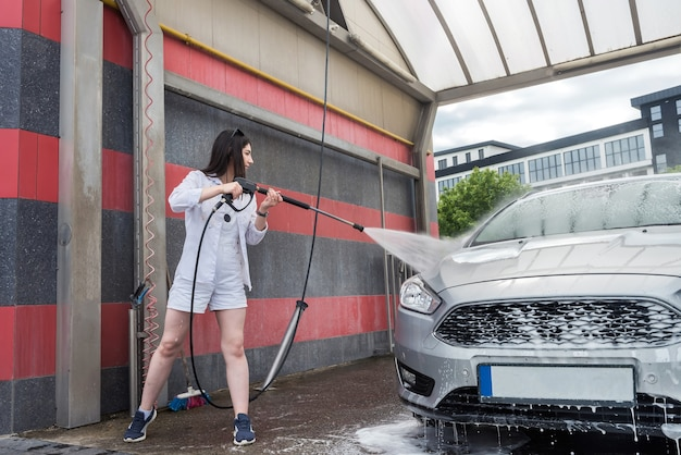 Ukraińska szczupła kobieta czyszczenie i mycie pianki jej samochód strumieniem wody