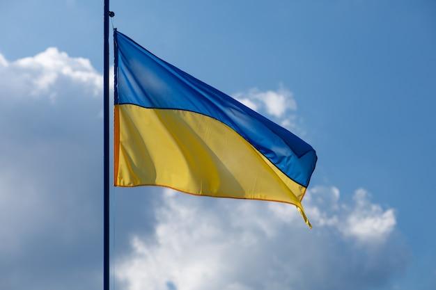Ukraińska żółta i niebieska flaga z niebem w tyle