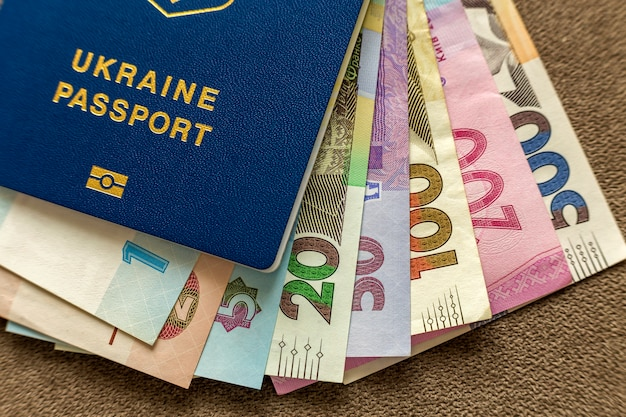 Ukraiński paszport i pieniądze, ukraińscy hryvna banknotów rachunki na kopii przestrzeni tle, odgórny widok. koncepcja problemów z podróży i finansów.