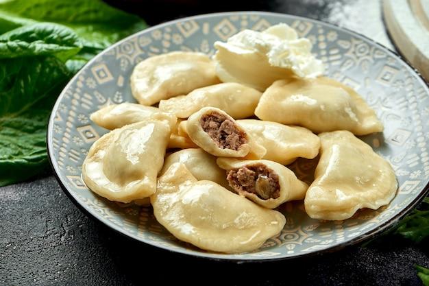 Ukraińskie lub polskie tradycyjne danie - pierogi lub varenyky (pierogi) nadziewane mięsem i kwaśną śmietaną. ciemny stół. zamknij się, selektywna ostrość