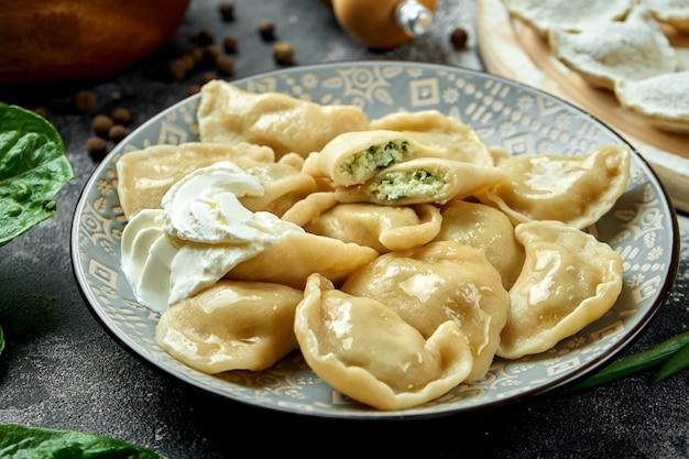 Ukraińskie lub polskie tradycyjne danie - pierogi lub varenyky (pierogi) nadziewane szpinakiem i serem ze śmietaną na ciemnym stole. zamknij się, selektywna ostrość