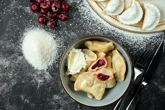 Ukraińskie lub polskie tradycyjne danie - pierogi lub varenyky (pierogi) nadziewane wiśniami i kwaśną śmietaną na ciemnym stole. zamknij się, selektywna ostrość