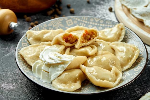 Ukraińskie lub polskie tradycyjne danie - pierogi lub varenyky (pierogi) z nadzieniem z kapusty i śmietany na ciemnym stole. zamknij się, selektywna ostrość