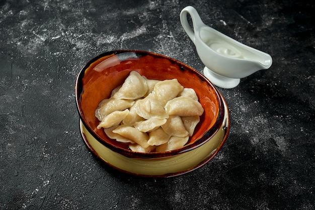Ukraińskie lub polskie tradycyjne danie - pierogi lub varenyky (pierogi) z solonym nadzieniem i kwaśną śmietaną na ciemnym stole.