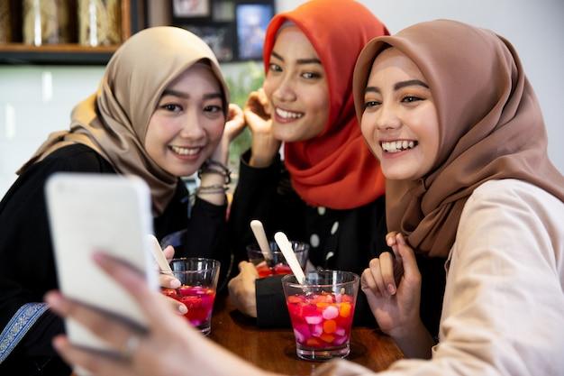 Ukryte młode kobiety relaksuje używać smartphone dla selfie