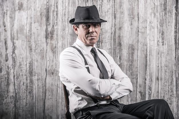 Ukryte zagrożenie. apodyktyczny starszy mężczyzna w gangsterskim stroju siedzi przy krześle i patrzy na kamerę na szarej ścianie w tle