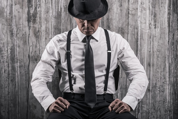 Ukryte zagrożenie. apodyktyczny starszy mężczyzna w gangsterskim ubraniu, siedzący przy krześle i przy ścianie