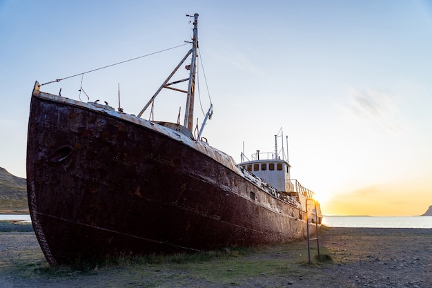 Ukryty statek wielorybniczy, który rozbił się na plaży do latrabjarg podczas zachodu słońca.