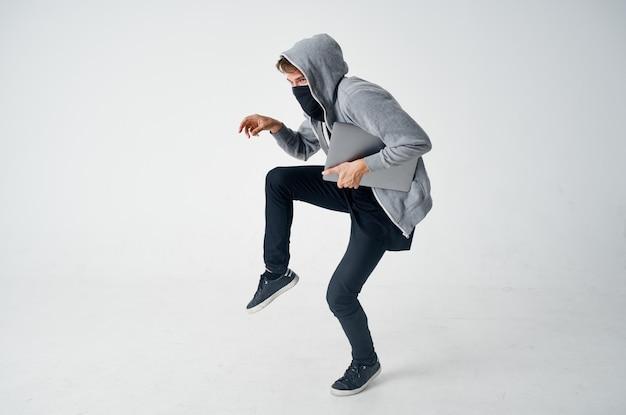 Ukryty zamaskowany mężczyzna laptop haker niebezpieczeństwo penetracji. wysokiej jakości zdjęcie