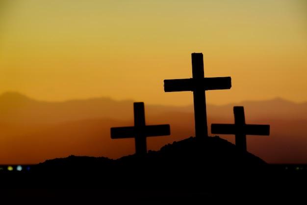 Ukrzyżowanie jezusa chrystusa o wschodzie słońca - sylwetka trzy krzyże na wzgórzu