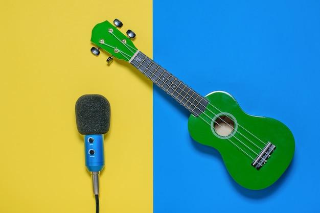 Ukulele i mikrofon z przewodami na niebieskim i jasnożółtym tle. widok z góry.