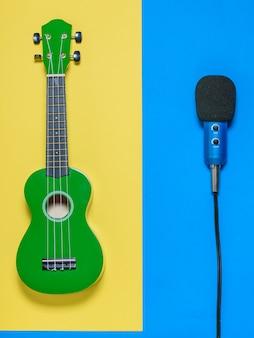 Ukulele i mikrofon z przewodami na niebieskim i żółtym tle. widok z góry.