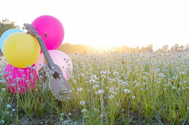 Ukulele postawione na trawie kwiatowej z balonami o pięknym świetle