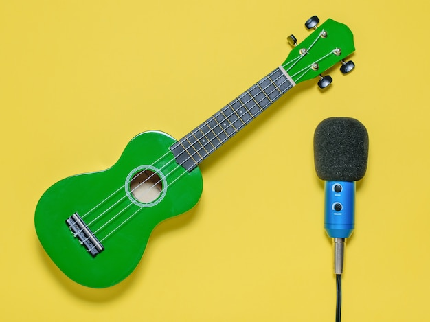 Ukulele ukulele ukulele i niebieski mikrofon przewodowy. widok z góry.