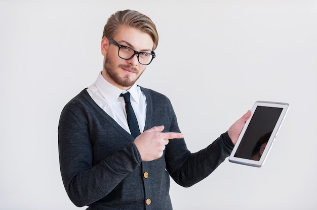 Ułatwi ci to życie. przystojny młody mężczyzna w okularach trzymający cyfrowy tablet i wskazujący go, stojąc na szarym tle