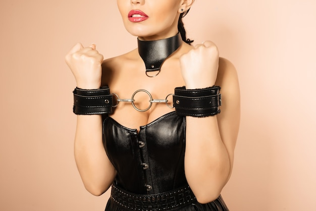 Uległa dziewczyna w skórzanym czarnym gorsecie, kajdankach i kołnierzu czeka na karę.