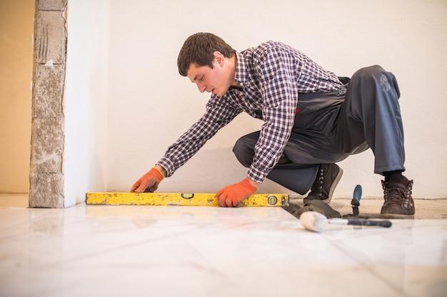 Ulepszanie płytek domowych - złota rączka z poziomicą układającą podłogę z płytek