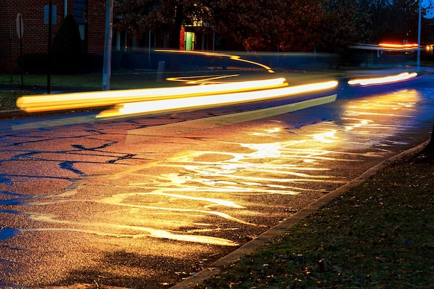 Ulewa w wielkim mieście nocne światło z witryn sklepowych odbijało się na drodze, po której jeżdżą samochody...
