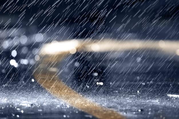 Ulewny deszcz lub ulewa, krople deszczu spadają na asfalt, w nocy lub wieczorem.