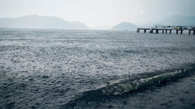 Ulewny deszcz nad plażą morską i drewnianym molo.