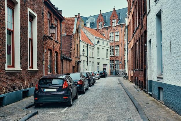 Ulica brugge z brukowaną drogą z zaparkowanymi samochodami i starymi średniowiecznymi domami brugia belgia