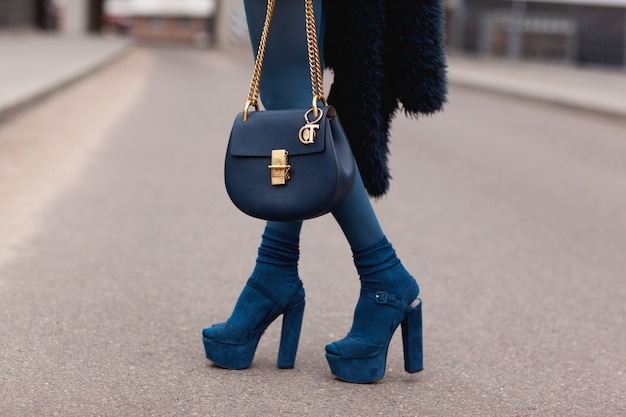 Ulica, jasny styl. młoda dziewczyna w błękitnym futerkowym żakiecie z torebką w piętach. detale.