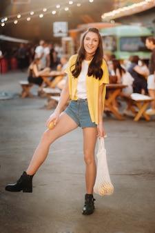 Ulicą miasta spaceruje dziewczyna w żółtej koszuli, szortach i czarnych butach z siateczką z cytryny i soku z cytryny. kobieta z koktajlem w dłoniach.