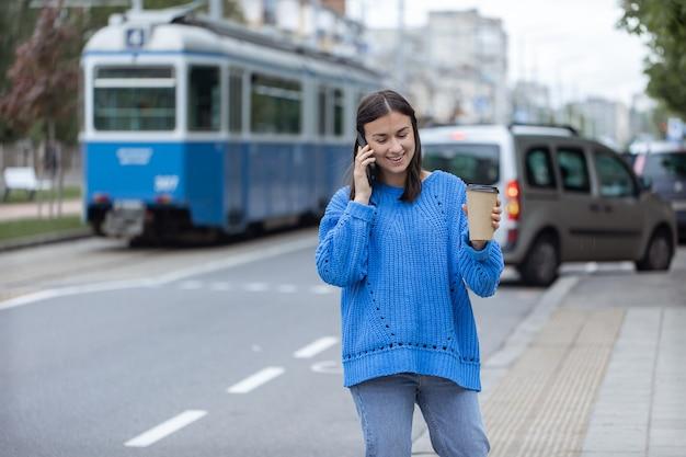 Ulica portret młodej kobiety rozmawia przez telefon w mieście w pobliżu jezdni.