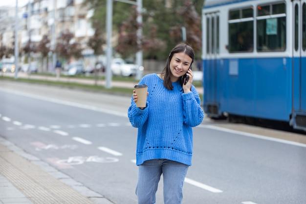 Ulica portret młodej kobiety rozmawiającej przez telefon w mieście w pobliżu jezdni