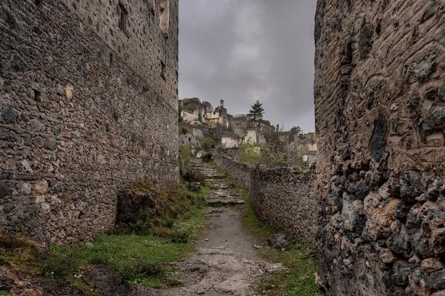 Ulica w opuszczonej greckiej wiosce kayakoy w turcji i ponure niebo