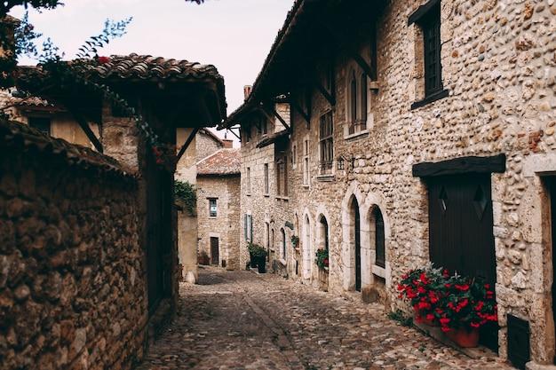 Ulica z fasadami starych kamiennych budynków w perouges we francji, czerwone róże. wysokiej jakości zdjęcie