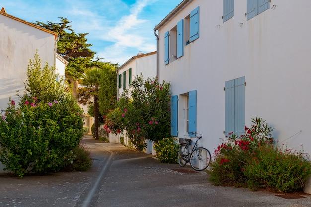 Ulica z żywymi kolorami kwiatów i klasycznym rowerem opartym o białą ścianę