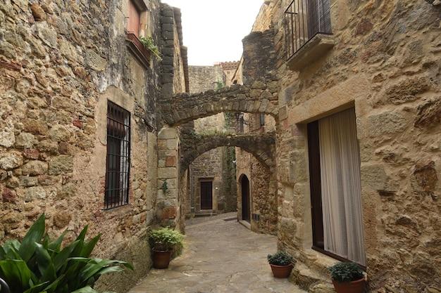 Ulice i łuk starego miasta średniowiecznej wioski pals, prowincja girona, katalonia, hiszpania