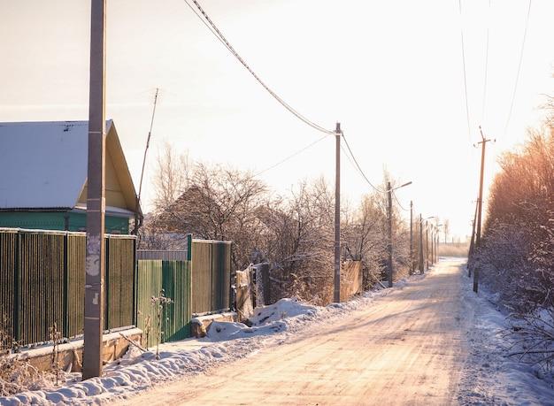 Ulice miasteczka pokryte śniegiem o zachodzie słońca
