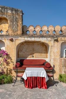 Uliczna kawiarnia na starym mieście, na zewnątrz w jaipur, radżastan, indie. stół, sofa i krzesła przy starej ścianie, z bliska