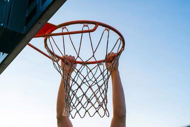 Uliczna koszykówka slam dunk konkurencji, zbliżenie gracza wiszącego na obręczy.