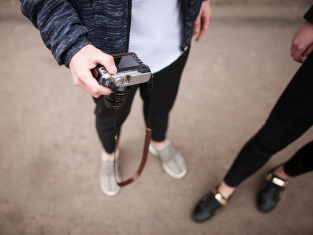 Uliczna sesja zdjęciowa. fotografowie w procesie. nie do poznania stylowi młodzi ludzie w selektywnym skupieniu, kreatywny styl życia widok z góry. nowoczesna elektronika