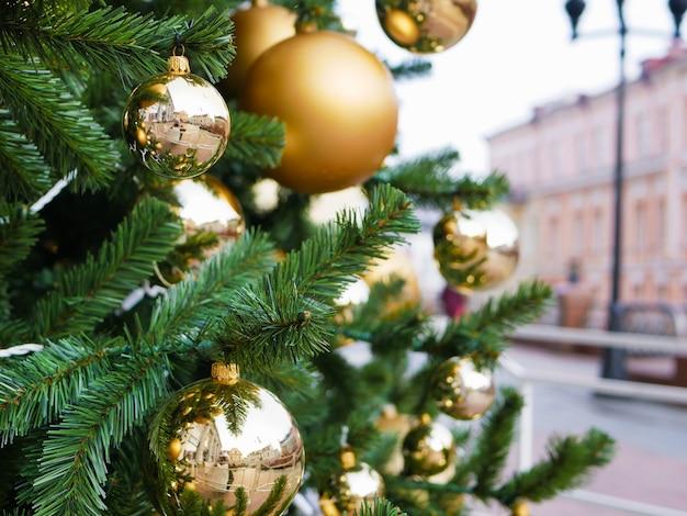 Uliczne drzewo ozdobione złotymi kulkami