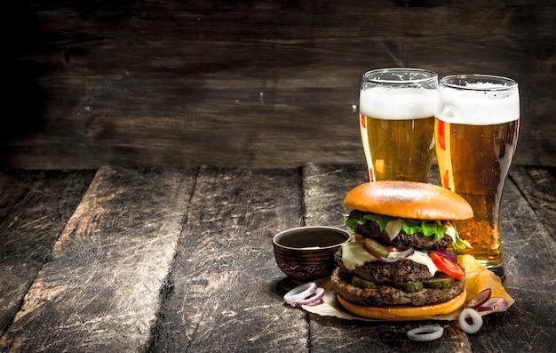 Uliczne jedzenie. duży burger z kieliszkami jasnego piwa. na drewnianym stole.