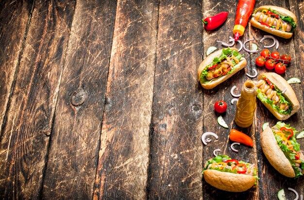 Uliczne jedzenie. hot dogi z musztardą, ostrym sosem, cebulą i zieleniną.