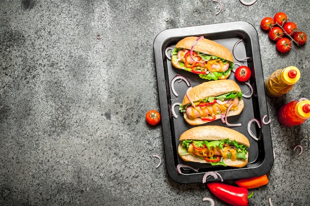 Uliczne jedzenie. hot dogi z ziołami i warzywami na patelni. na rustykalnym tle.