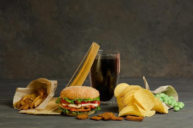 Uliczne jedzenie lub fast food. hamburger, frytki i cola na stole z drewnianym stołem. niezdrowy burger z wołowiną.